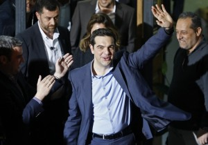 Head of radical leftist Syriza party Tsipras waves while leaving the party headquarters after winning the elections in Athens