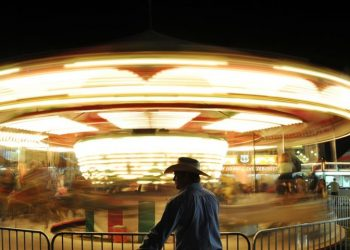 A man waits for his family as they ride the carousel in the carnival Saturday night at the Sheridan County Fairgrounds. The Sheridan Press|Justin Sheely.